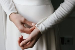 close up of woman fastening button on simple silk wedding dress
