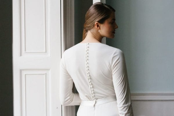 close up shot of woman wearing simple silk wedding dress high neck long sleeve