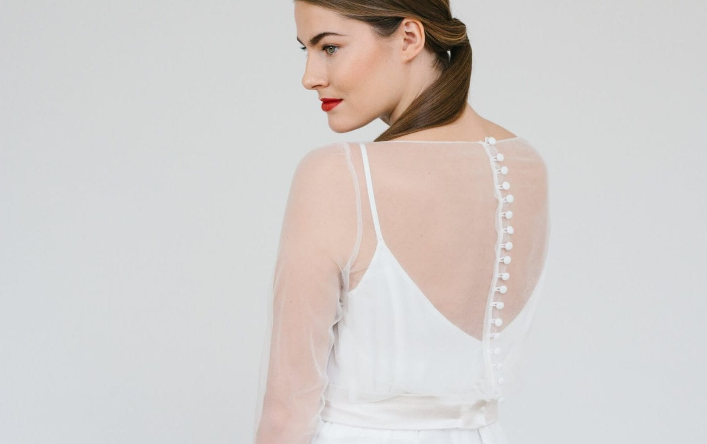 back shot of thin strap simple silk wedding dress with sheer bridal top