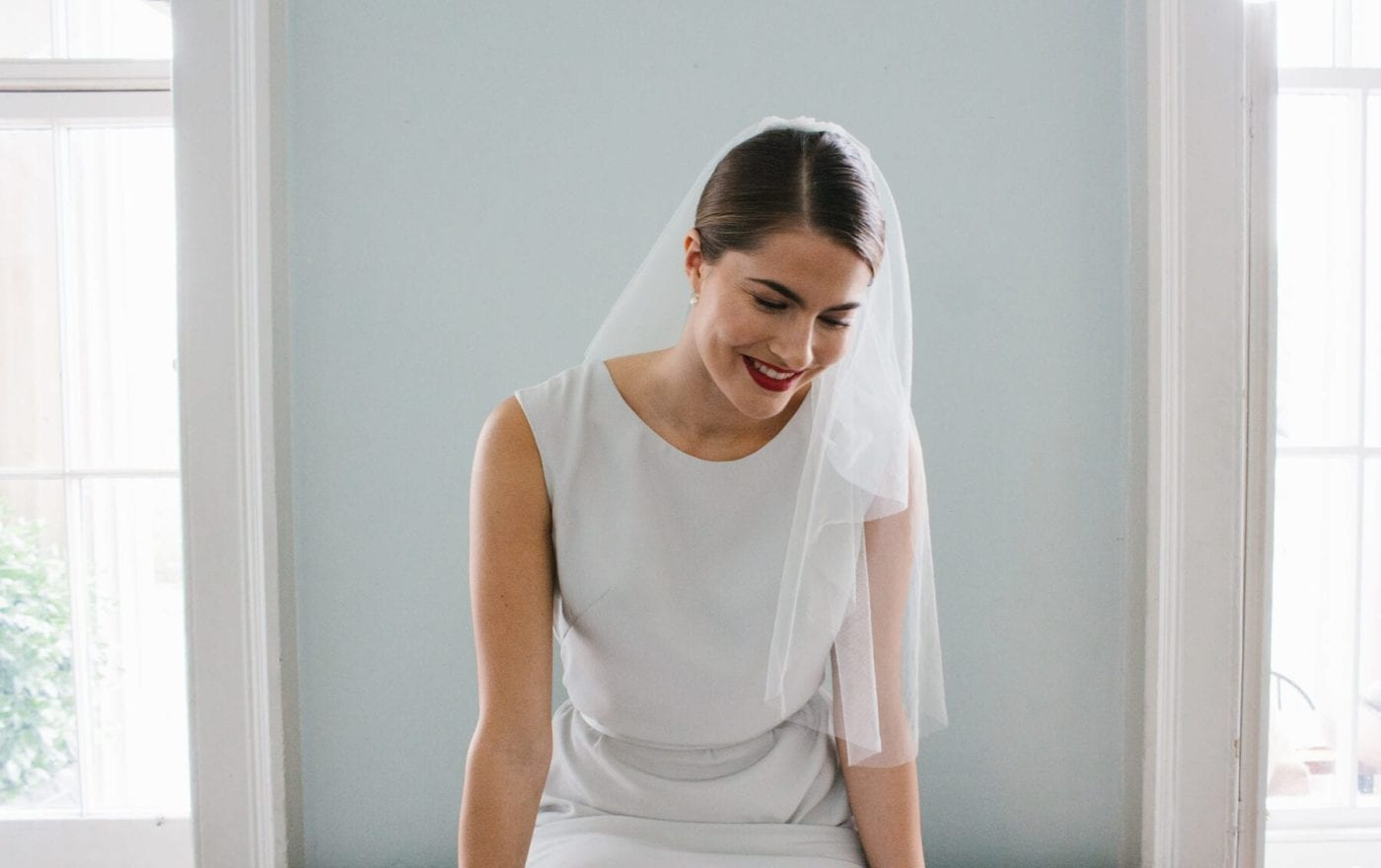 close up shot of woman wearing short wedding veil and high neck sleeveless white silk wedding dress