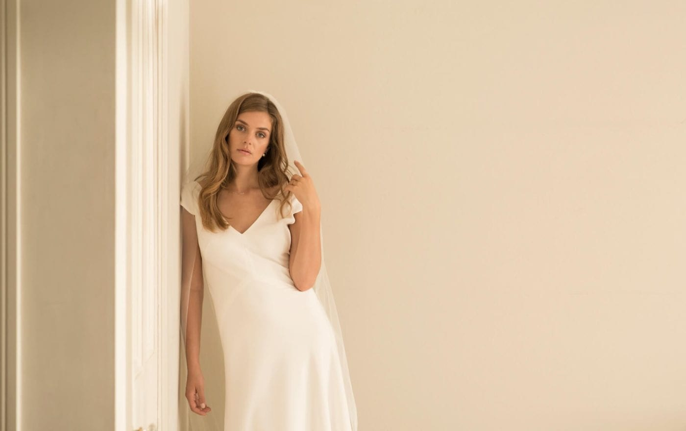 woman wearing cap sleeve v neck wedding dress with veil