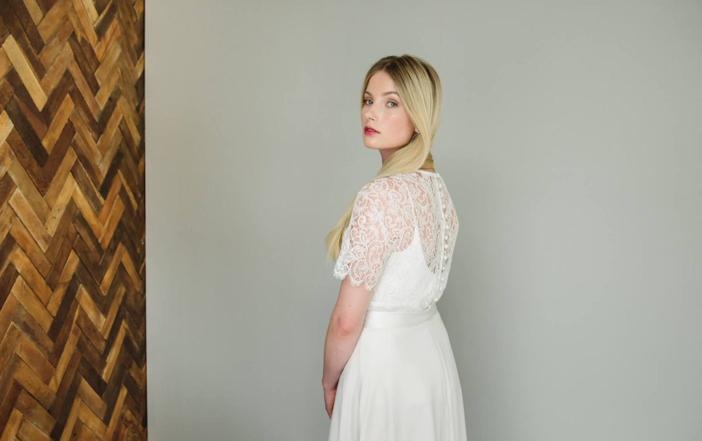 back shot of simple silk wedding dress with lace bridal top