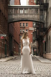 bride wearing deep v neck wedding dress with lace overlay stood in street