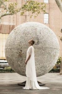woman wearing long white wedding dress and geometric lace wedding cape