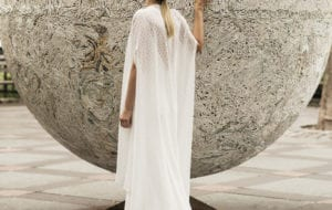 woman wearing lace bridal cape over wedding dress standing by statue