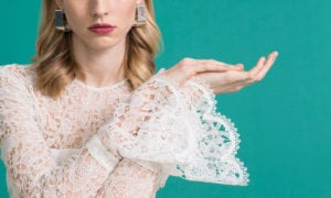 close up of woman wearing lace bridal top with ruffle sleeves
