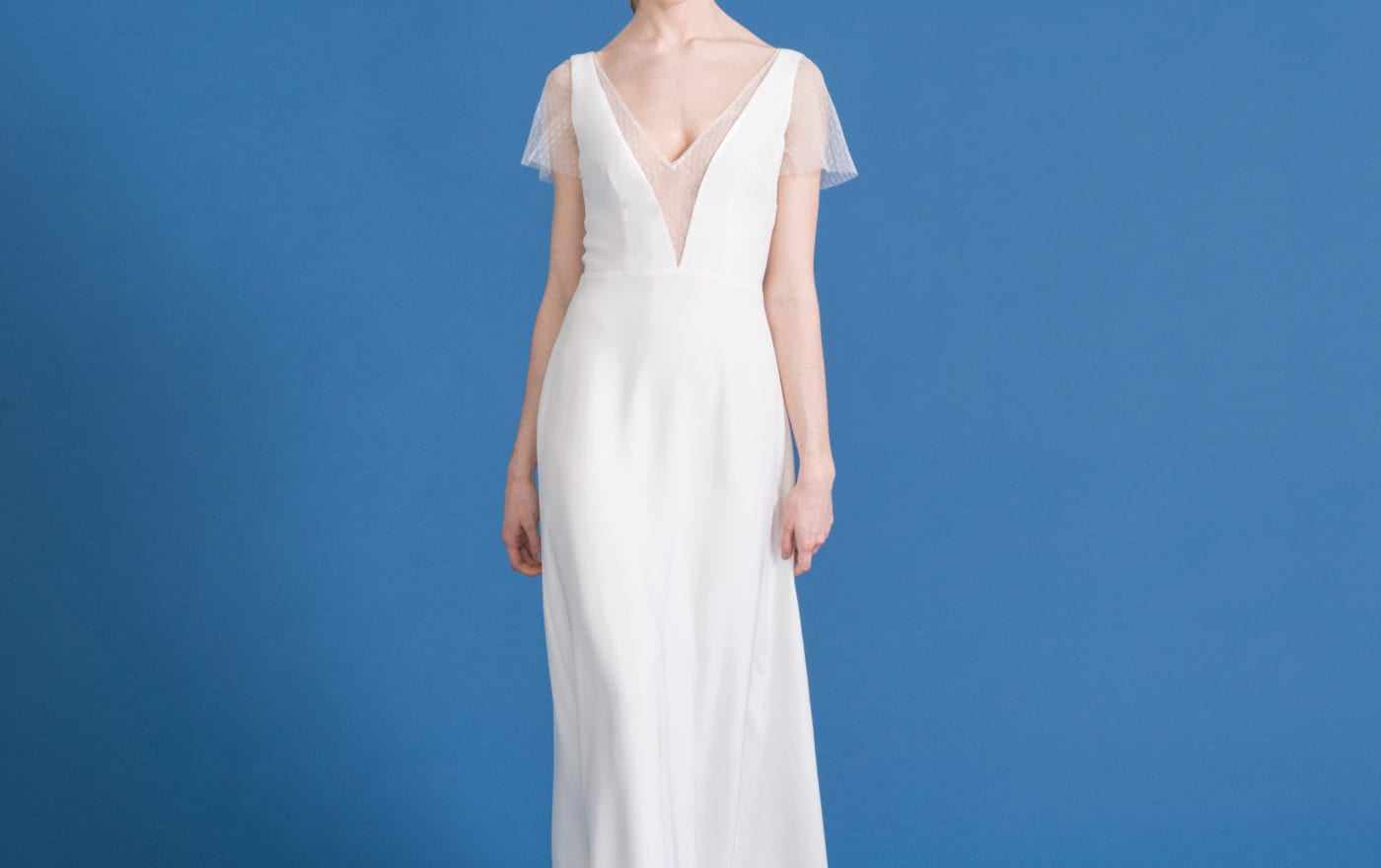 deep v neck wedding dress with sheer overlay and cap sleeve