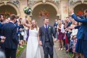 bride and groom walking down aisle with confetti