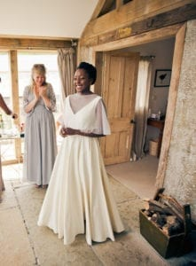 bride trying on ivory silk wedding dress
