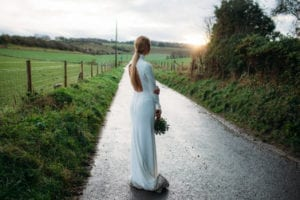 Woman on country road wearing portrait back high neck wedding dress