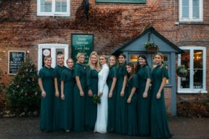 bride in white high neck wedding dress with bridesmaids in front of English pub