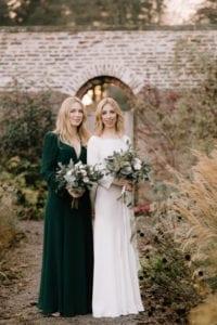 bride wearing high neck wedding dress with bridesmaid in dark green dress