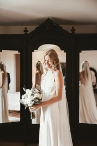 bride wearing high neck wedding dress with long bridal veil