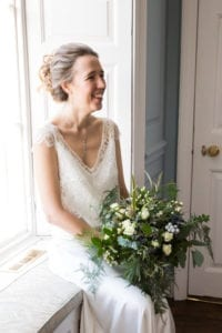 bride wearing lace bridal top over silk wedding dress sat on windowsill