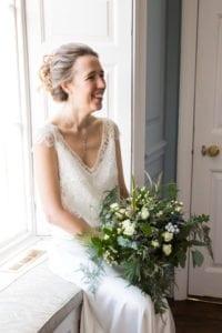 bride wearing lace bridal top over silk wedding dress sat on windowsill