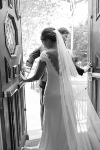 bride wearing low back wedding dress with lace cathedral veil walking out door
