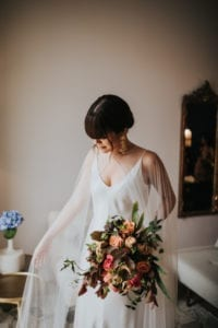 bride wearing simple silk wedding dress with long opaque bridal cape
