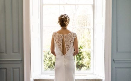 bride wearing simple wedding dress with bridal top looking out window