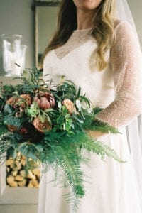 close up of bride wearing strappy wedding dress with lace bridal top holding bouquet