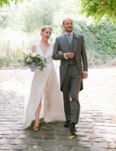 groom and bride wearing silk wrap wedding dress with sheer long bridal cape