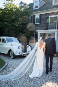 groom and bride wearing cathedral wedding veil walking away