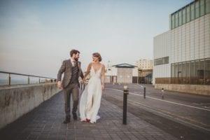 groom and bride wearing deep v neck wedding dress with silk overskirt walking down street