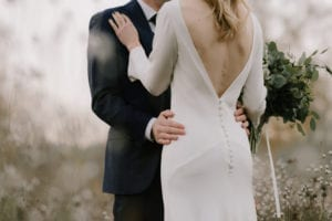 groom holding bride wearing low back long sleeve wedding dress