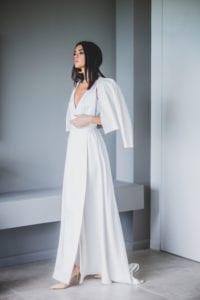 model wearing deep v neck wrap wedding dress and ivory leather bridal jacket