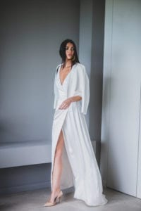 model wearing silk wrap wedding dress with leather bridal jacket